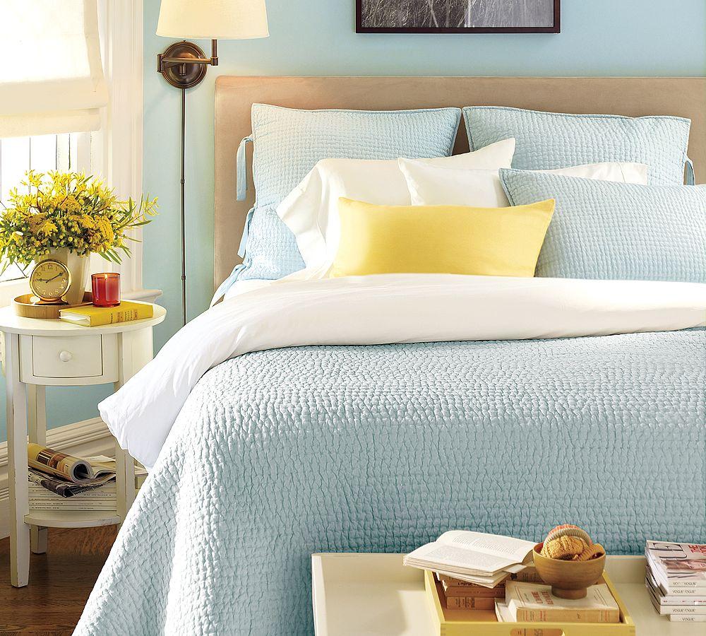 Голубое одеяло, подушки и стены в спальне