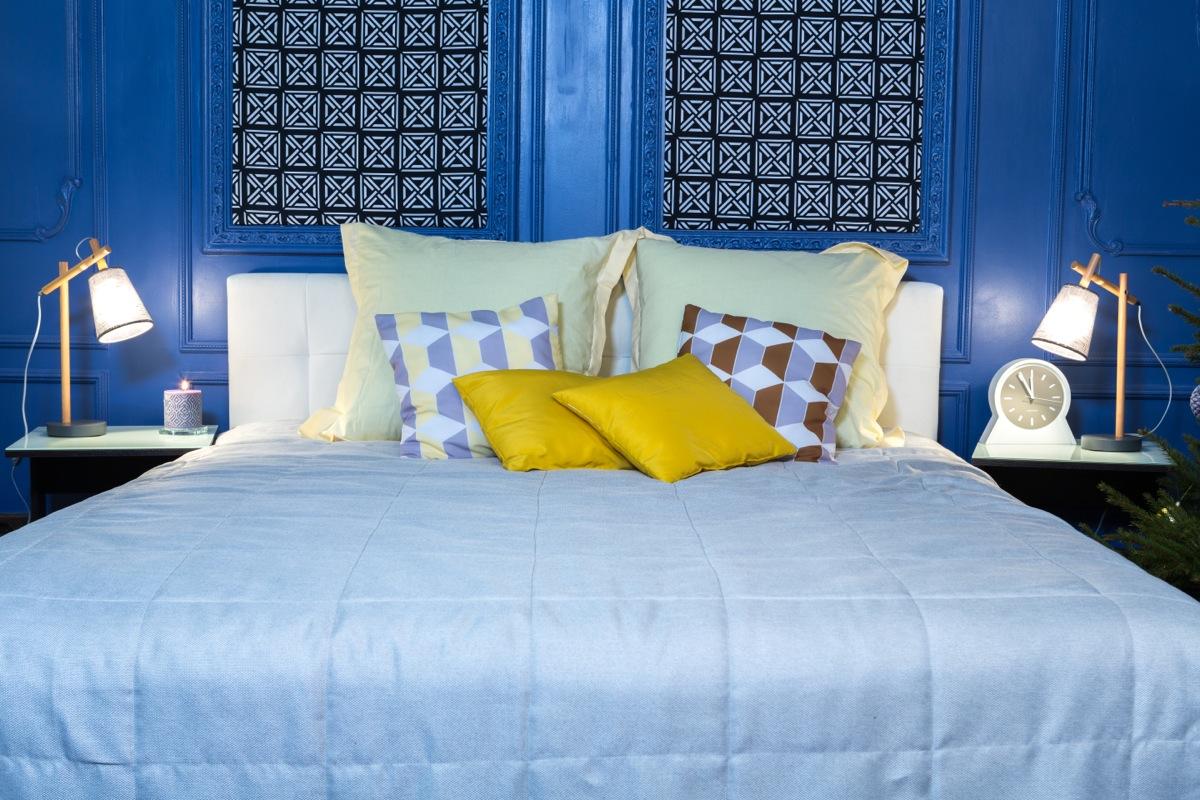 Желтые подушки и голубое покрывало в спальне