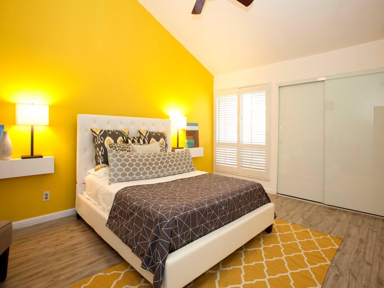 Спальня с желтой стеной в мансарде