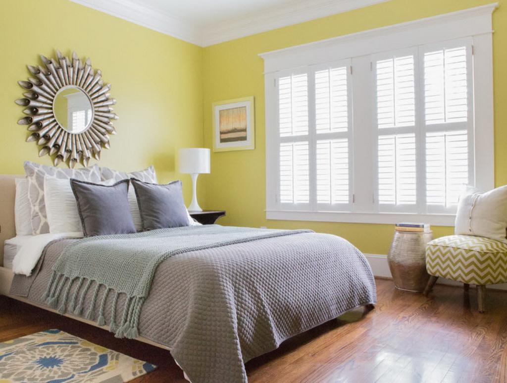 Серая кровать и бело-желтое кресло в спальне