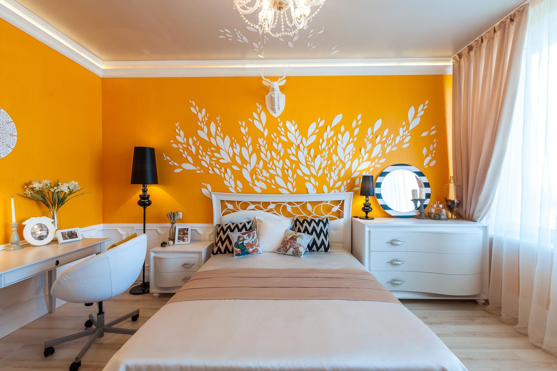 Люстра, торшер и настольная лампа в бело-желтой спальне