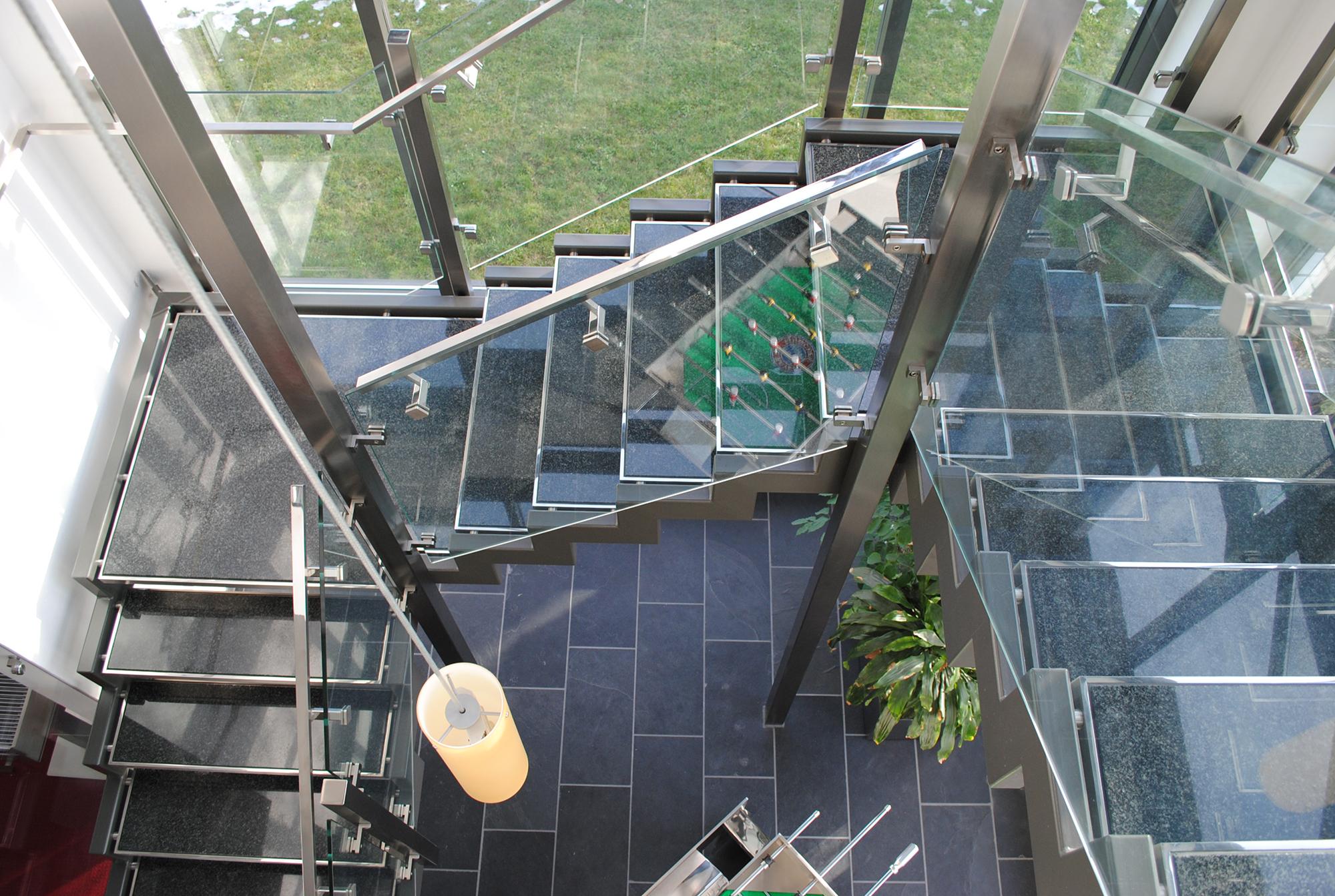 Поворотная лестница со стеклянными ограждениями в интерьере