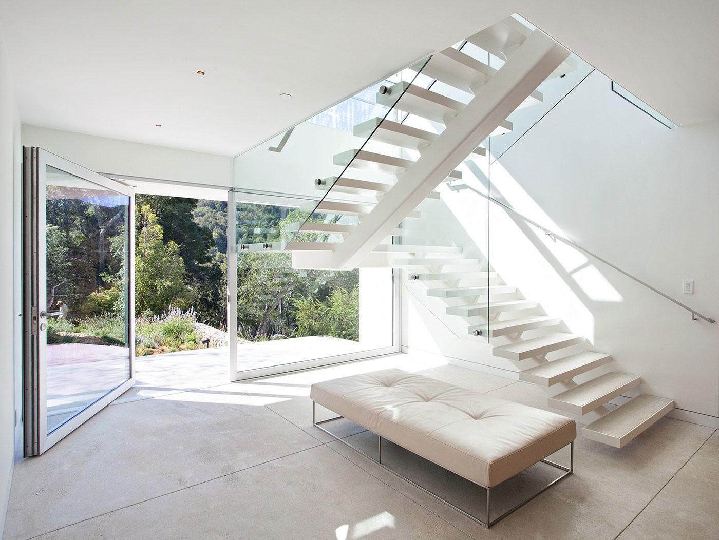 Белая лестница со стеклянными ограждениями в интерьере