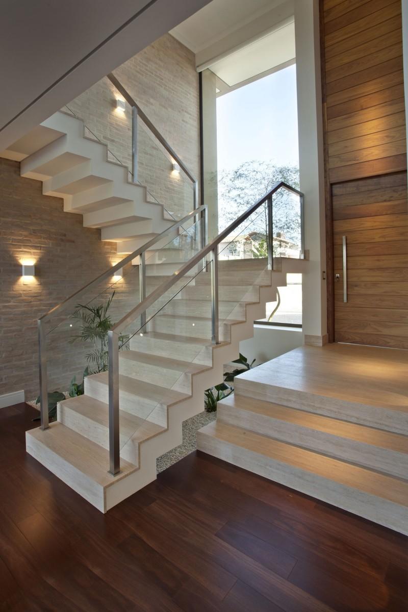 Бежевая лестница со стеклянными ограждениями в интерьере