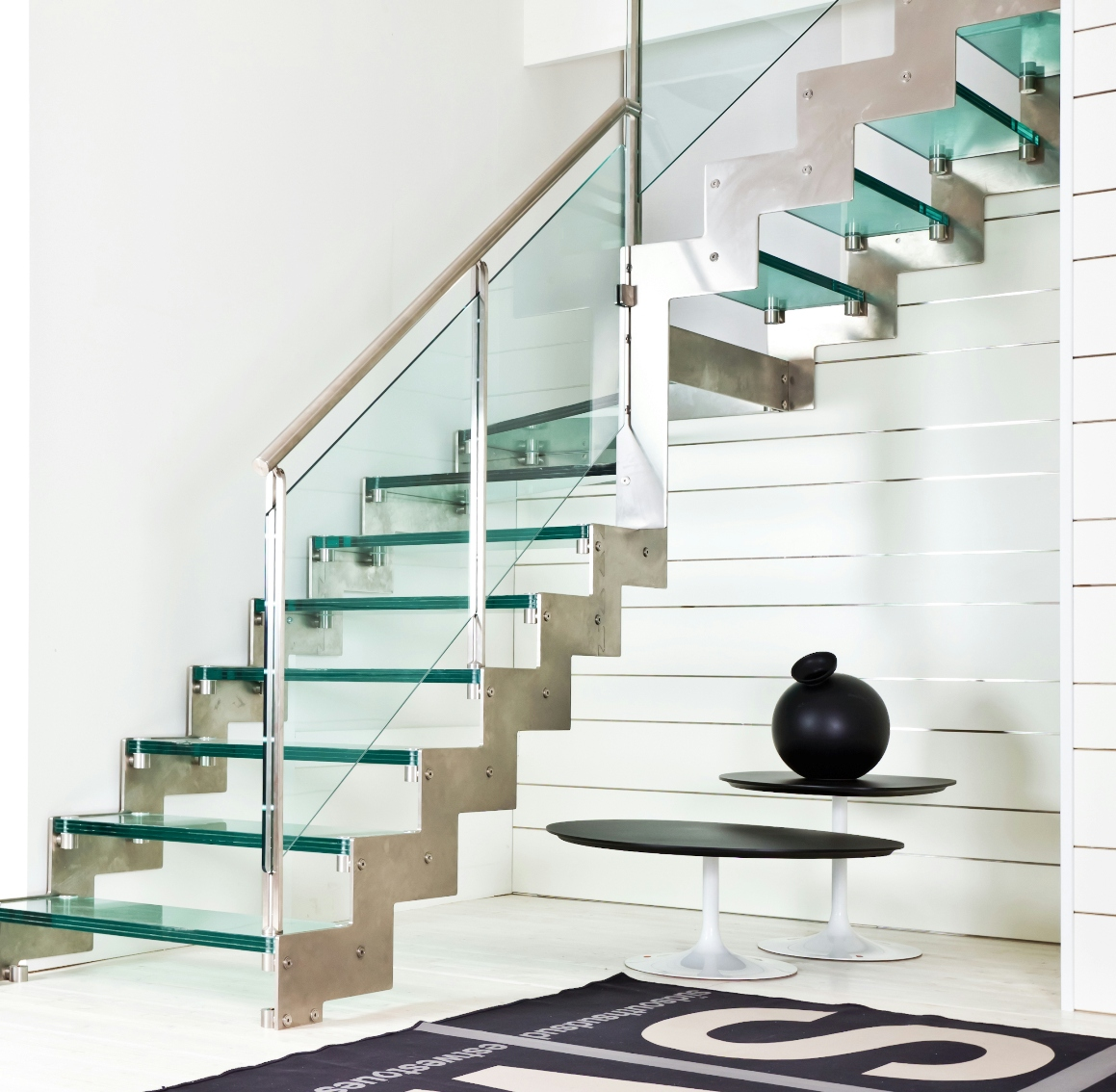 Поворотная лестница из металла и стекла в интерьере