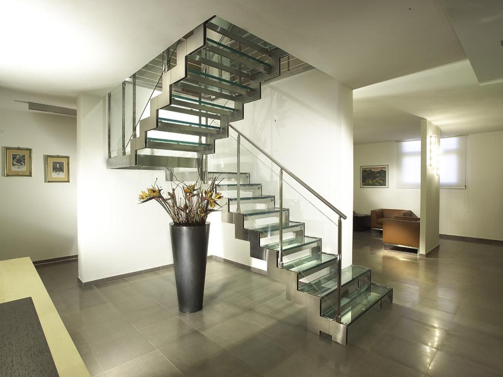 Поворотная лестница из металла и стекла в доме