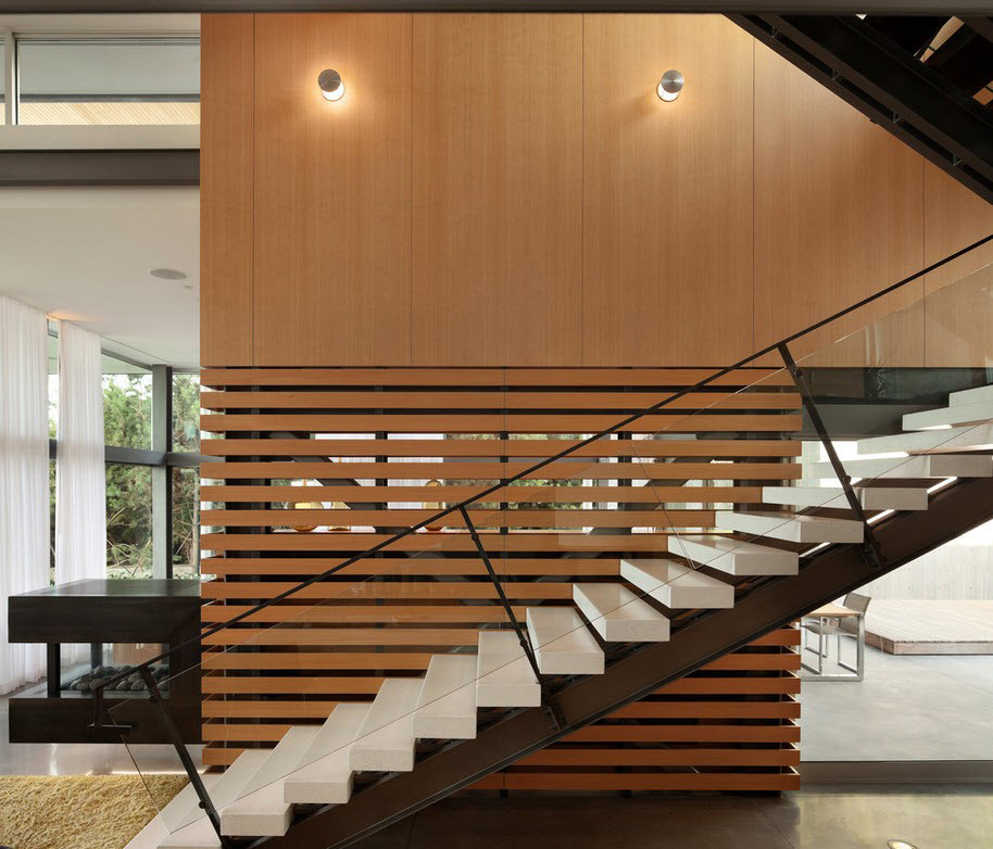 Черно-белая лестница со стеклянным ограждением в интерьере дома