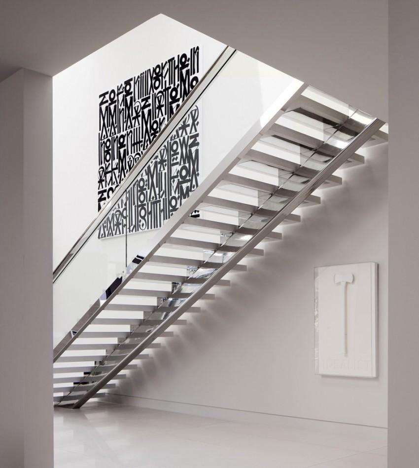 Металлическая лестница со стеклянным ограждением в интерьере дома