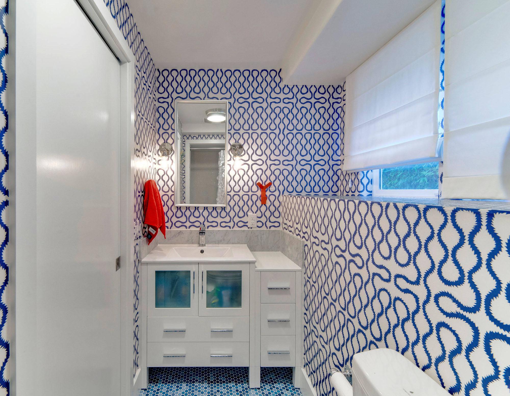 Красные полотенца в бело-синей ванной
