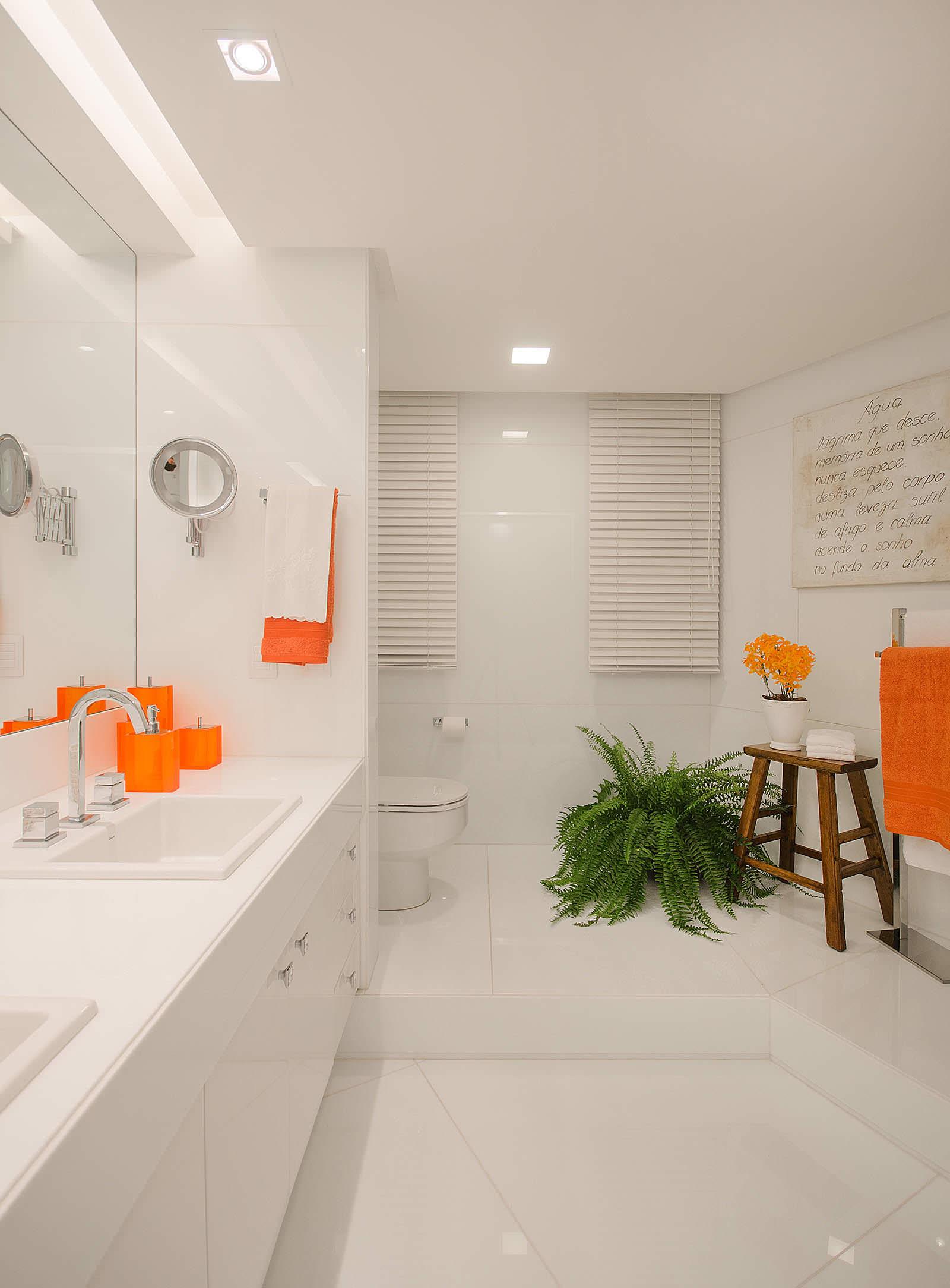 Оранжевые аксессуары в белой ванной
