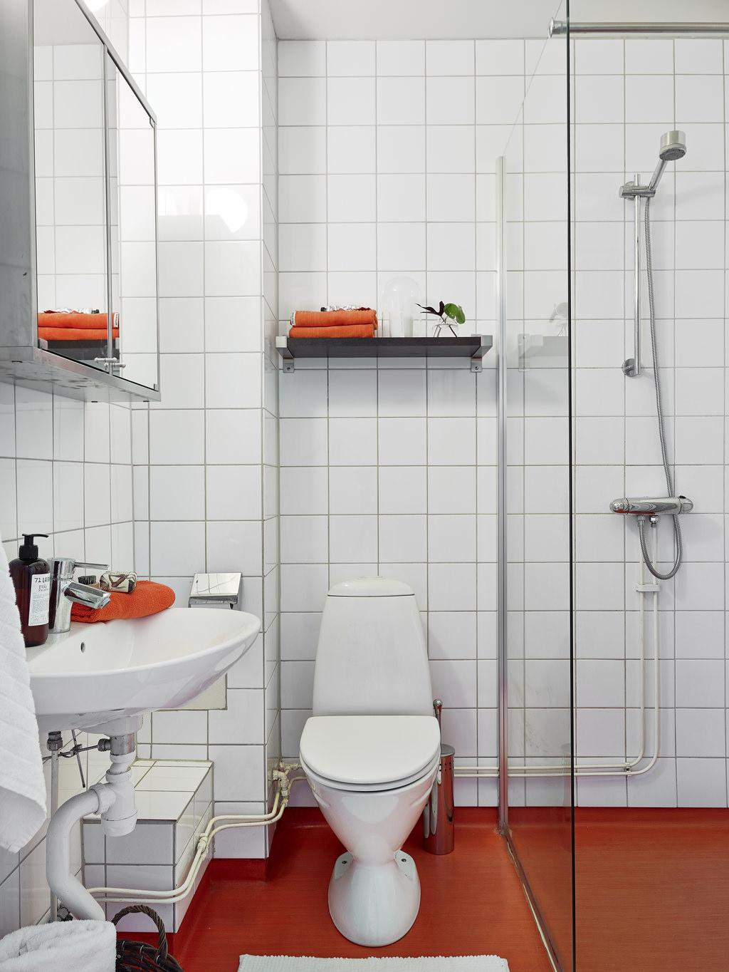 Оранжевые аксессуары и пол в белой ванной