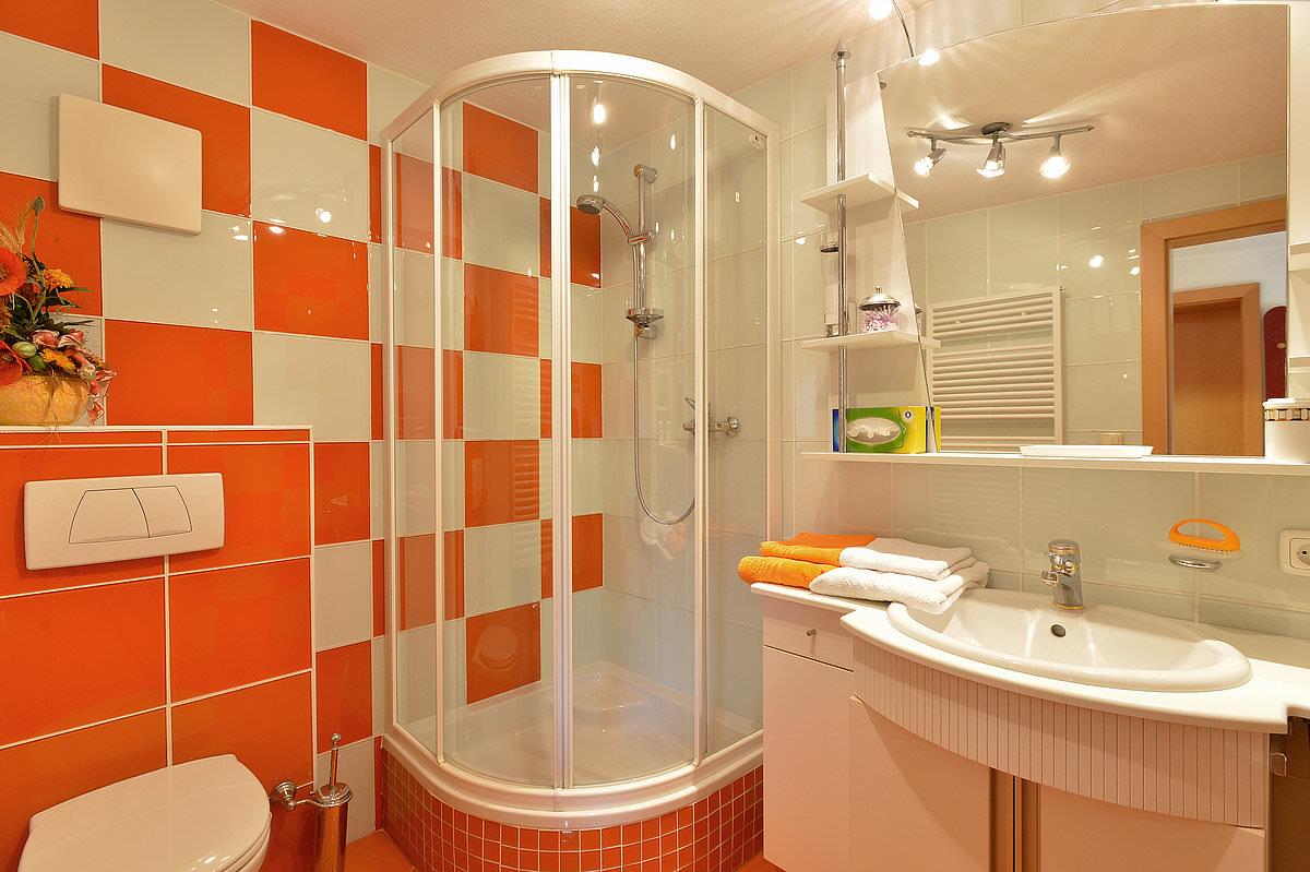 Белая сантехника в оранжевой ванной