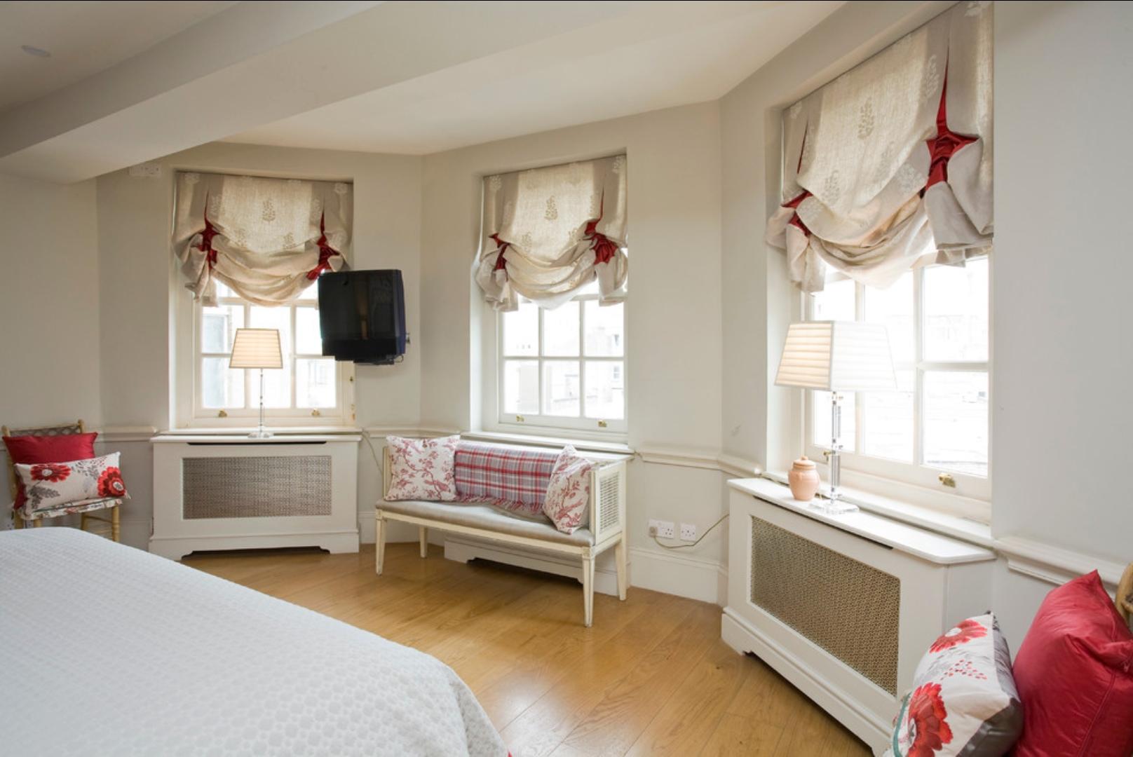 Красно-белые австрийские шторы в спальне
