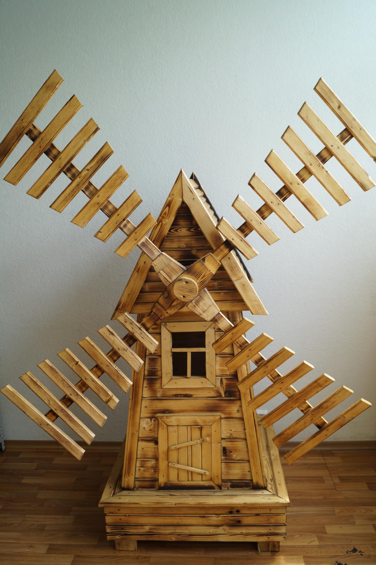 Небольшая декоративная мельница из дерева для украшения территории дома