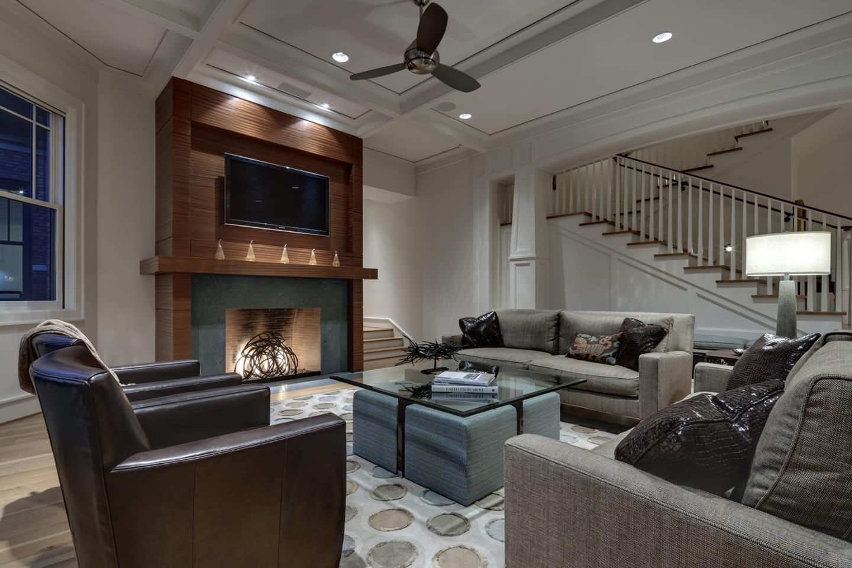 Серый диван еврокнижка в гостиной с камином