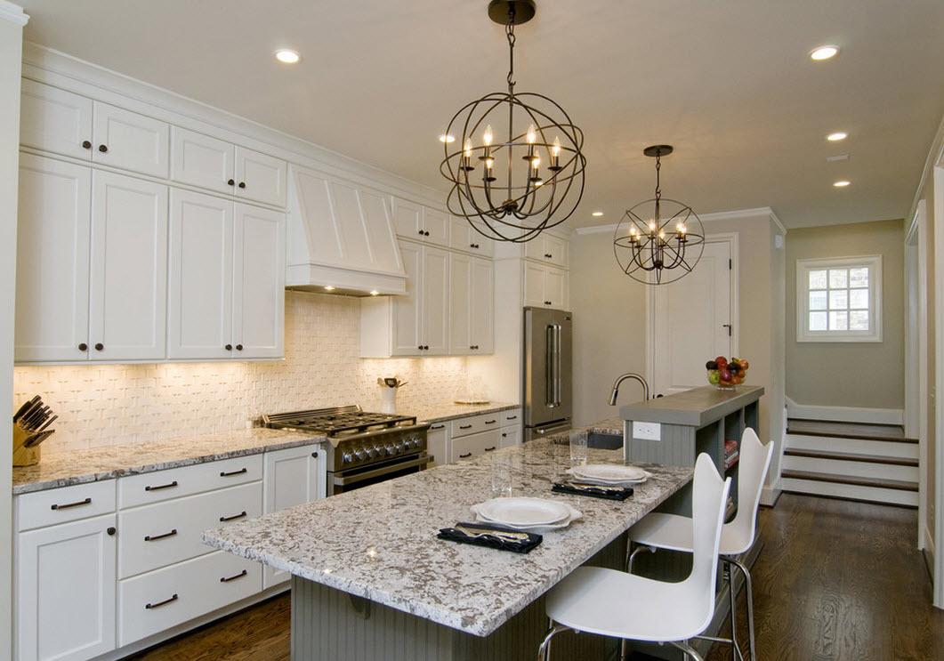 Круглая кованая люстра в интерьере светлой кухни