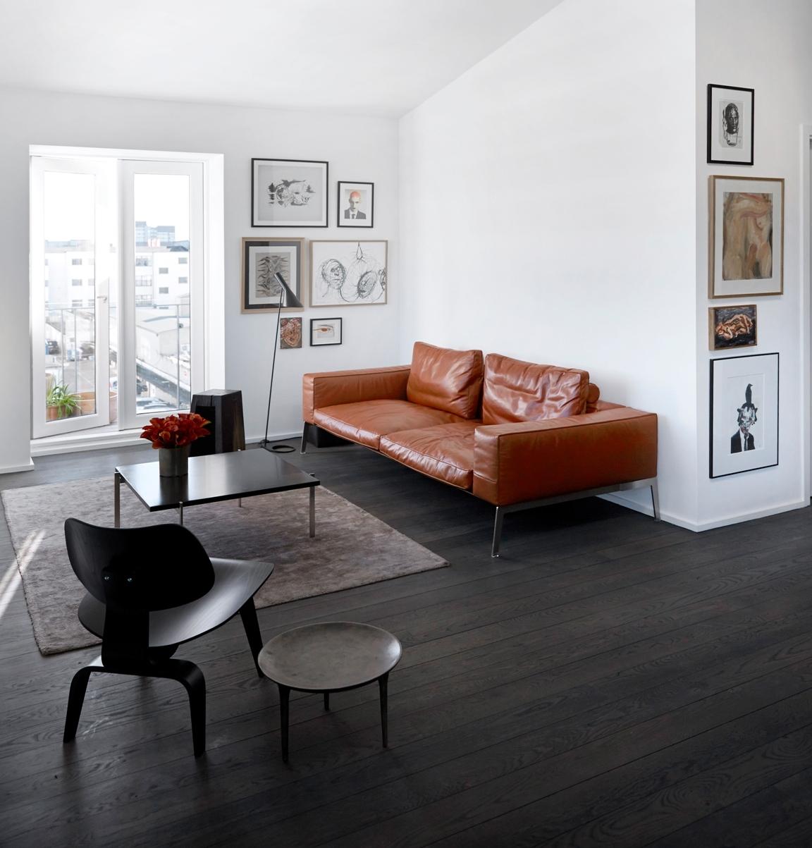 Темно-оранжевый кожаный диван в черно-белом интерьере