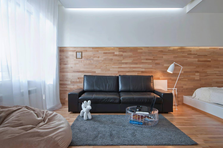 Черный кожаный диван в коричнево-белом интерьере