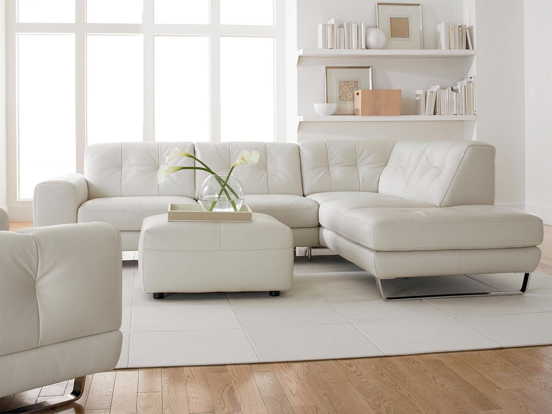 Белый кожаный угловой диван, кресло и пуф в интерьере