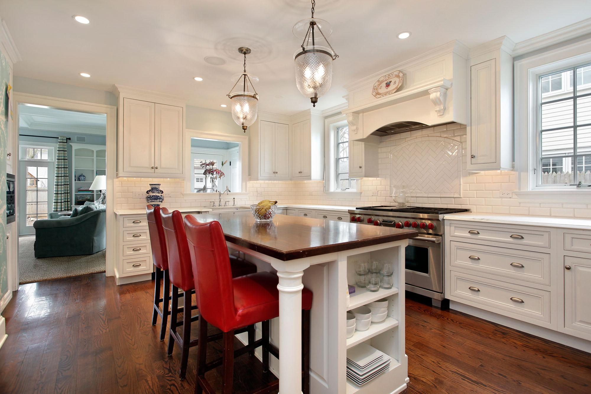 Красные стулья в бело-коричневой кухне