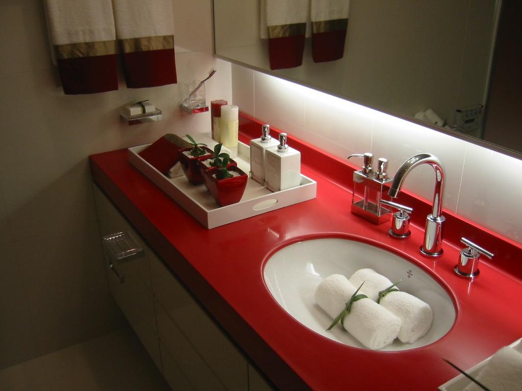 Красно-белая раковина из искусственного камня в интерьере ванной