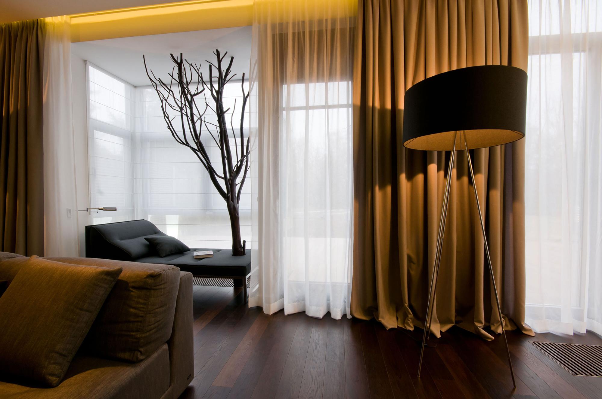 Плотные коричневые и белые прозрачные шторы в гостиной