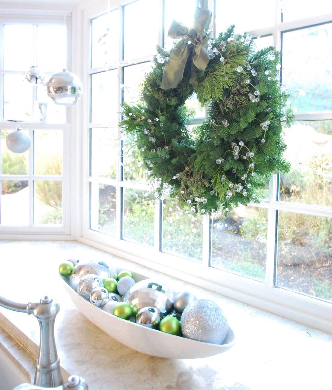 Оформление окна на Новый год венком и елочными игрушками
