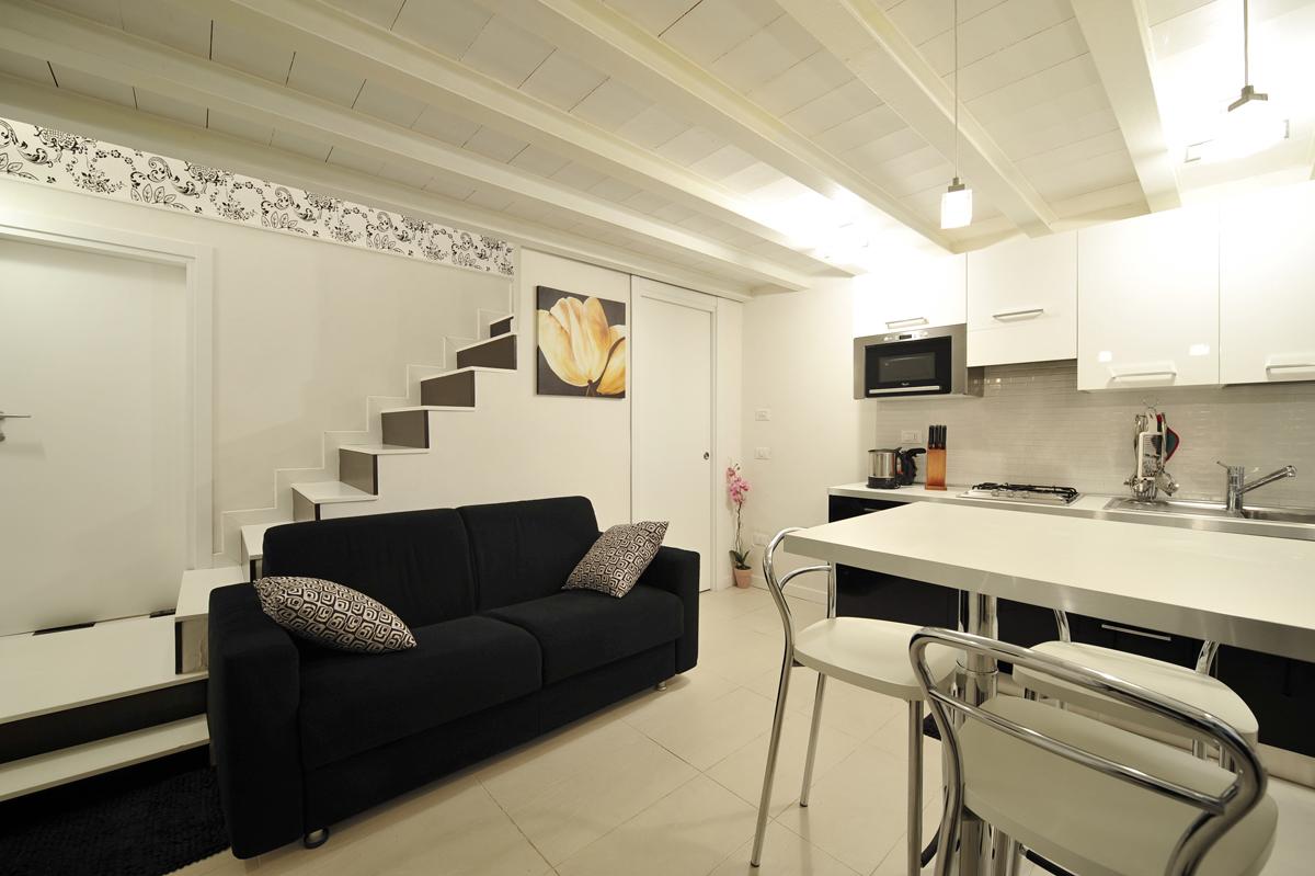 Черный диван в светлой кухне