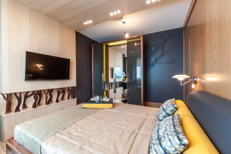 Желтые акценты в коричнево-черной спальне