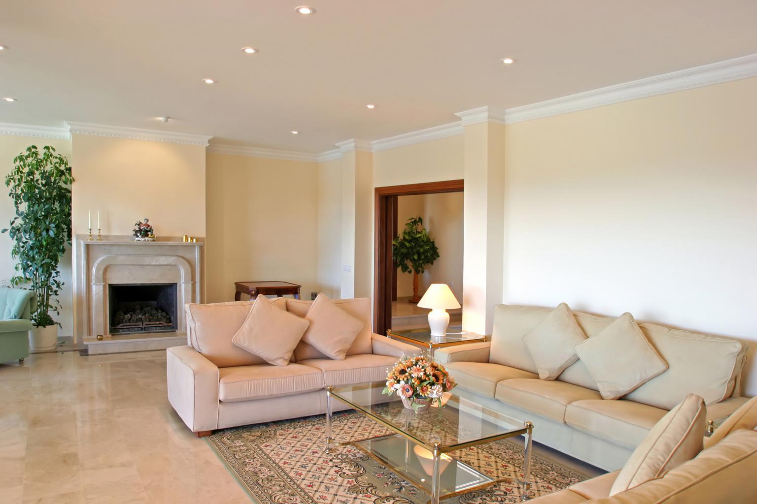 Простой потолок из гипсокартона с точечными светильниками в гостиной