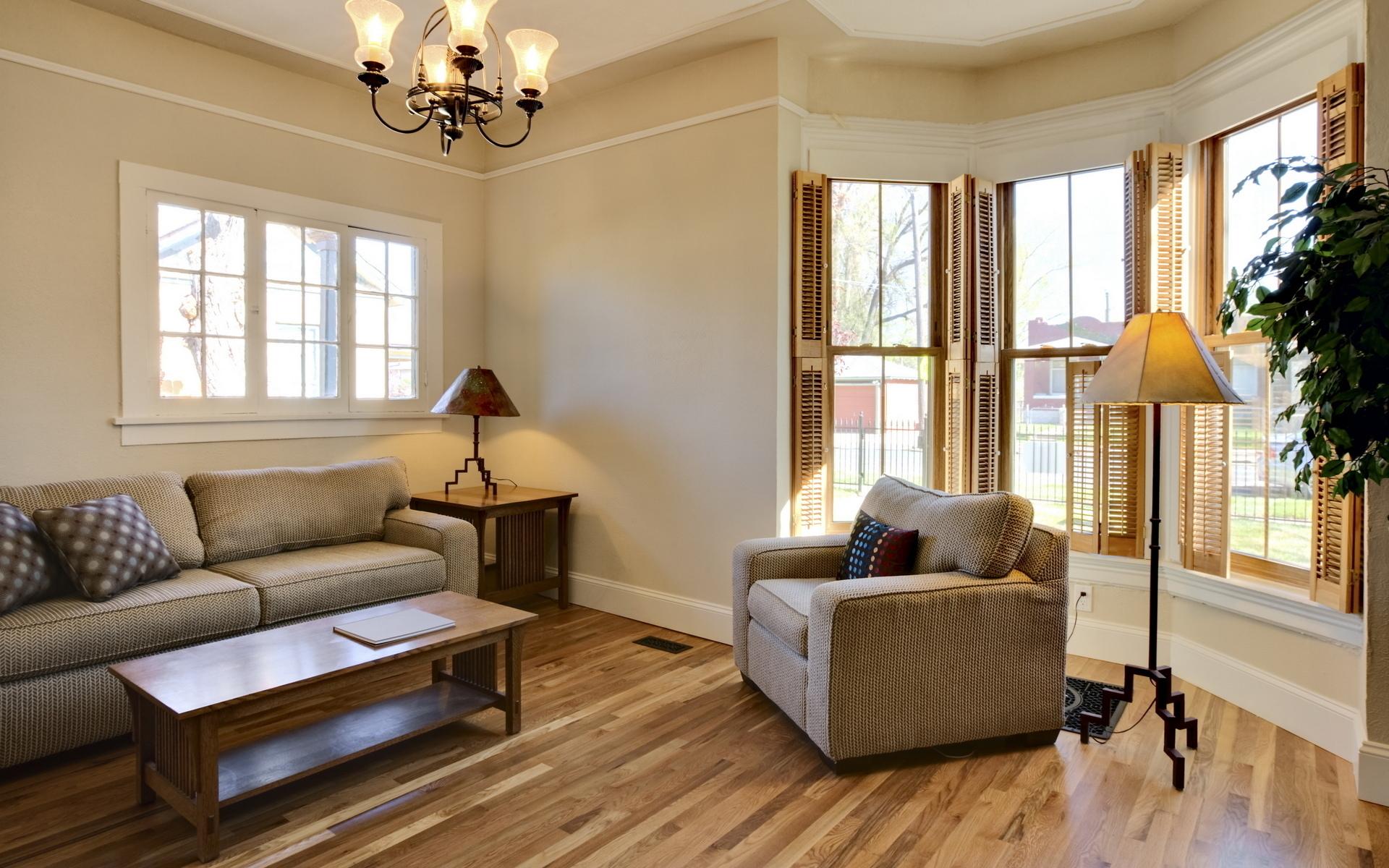 Люстра и настольные лампы в гостиной с двумя окнами