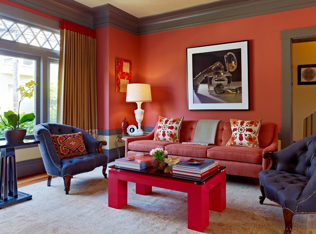 Красный диван, стол и отделка в гостиной