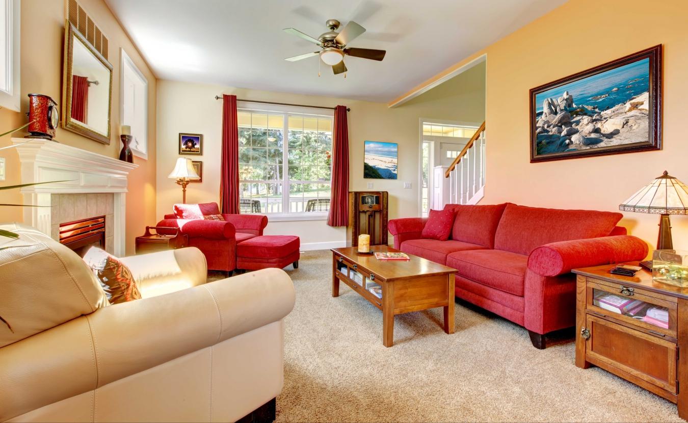 Красный диван, кресло и шторы в гостиной