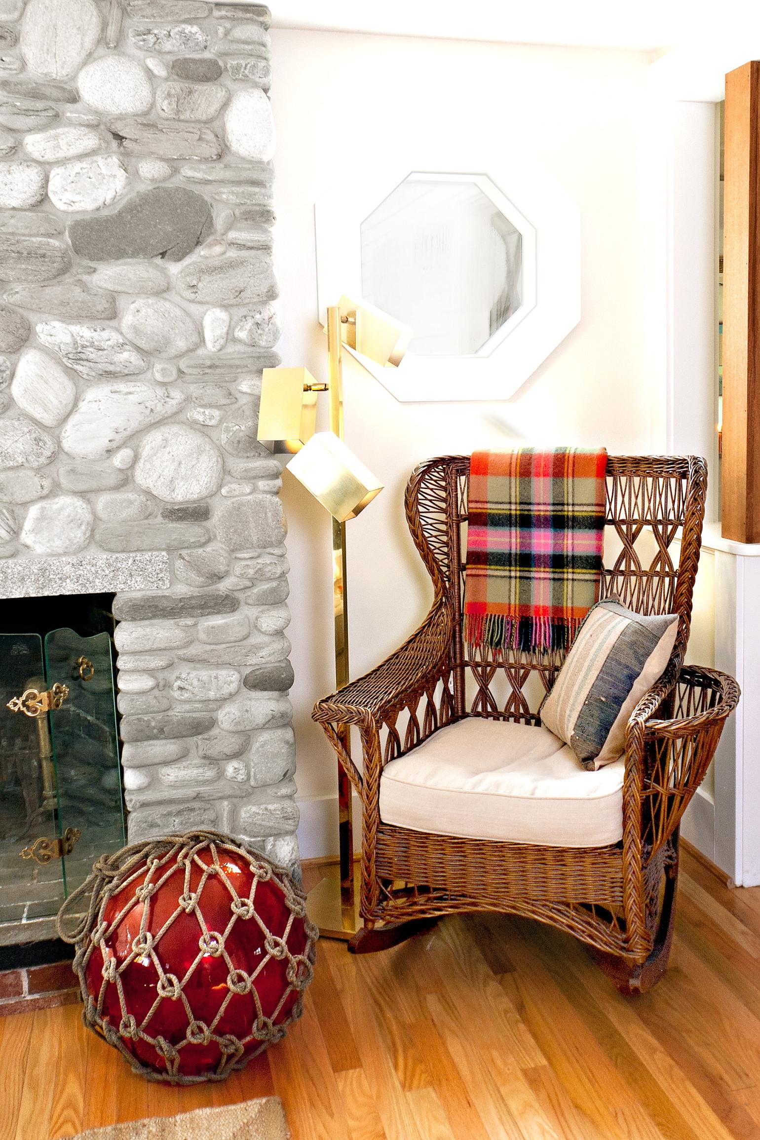 Красивое плетеное кресло-качалка в гостиной с камином