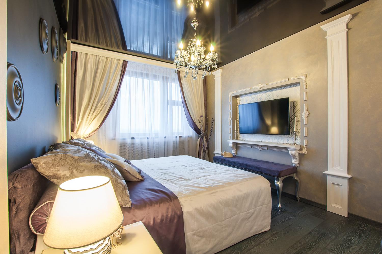 Классическая люстра с черным натяжным потолком в спальне