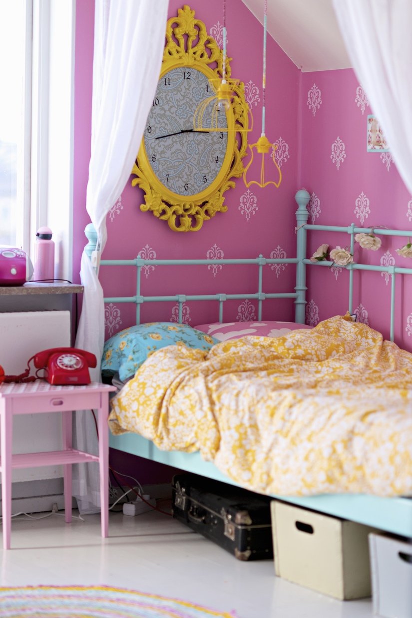 Розовые обои и золотистые часы в интерьере комнаты для девочки