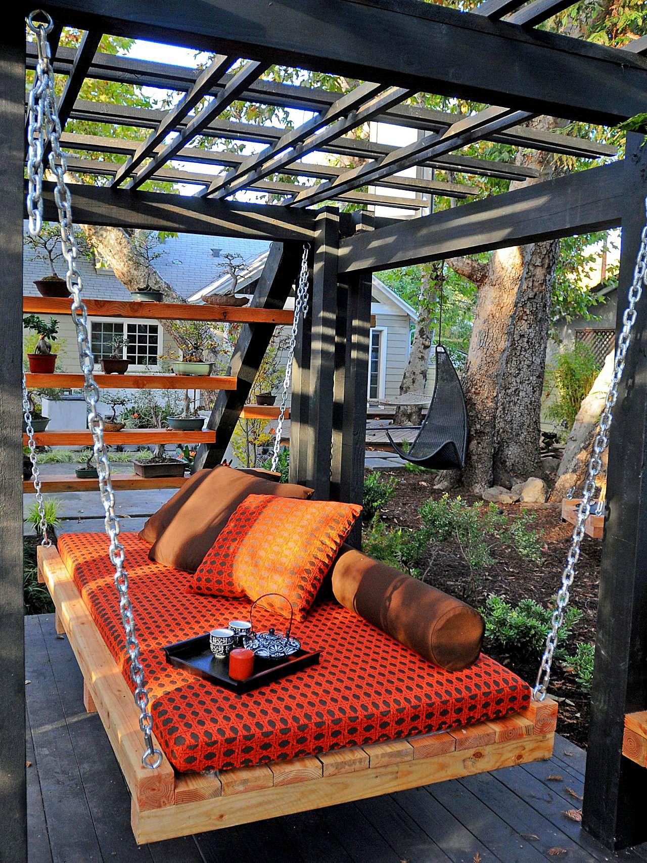 Подвесная деревянная кровать на участке дома