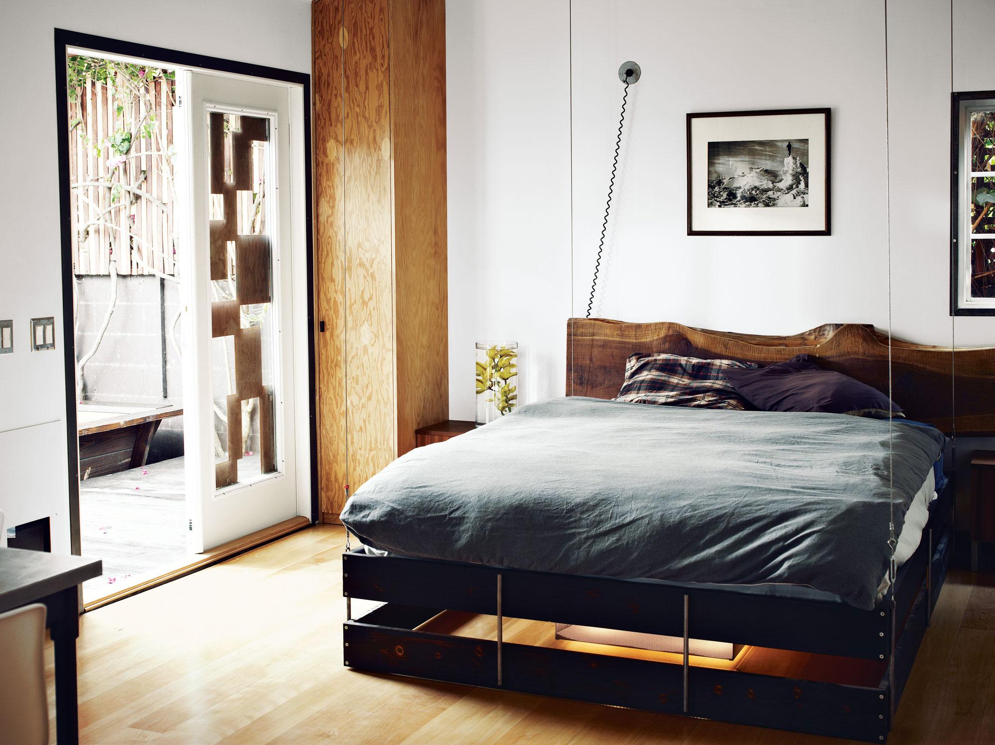 Подвесная черная деревянная кровать в спальне