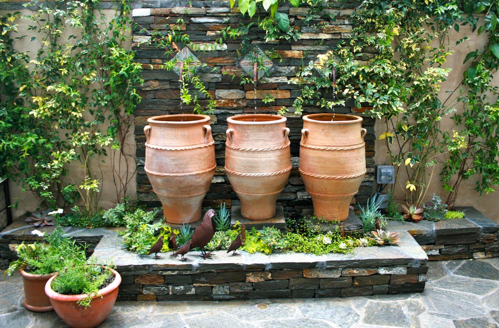 Красивые вазы и металлические статуэтки на участке