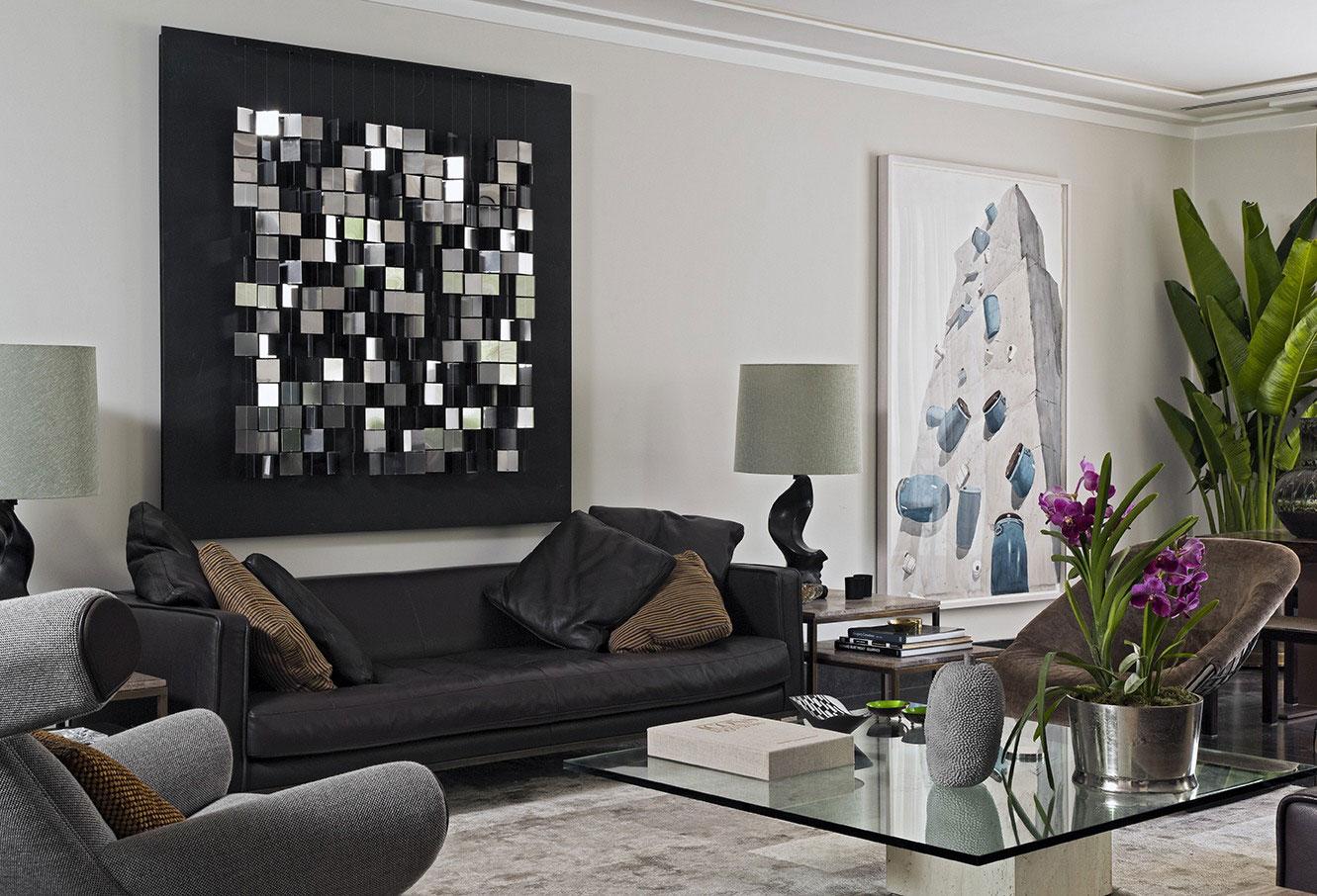 Черный кожаный диван в интерьере гостиной