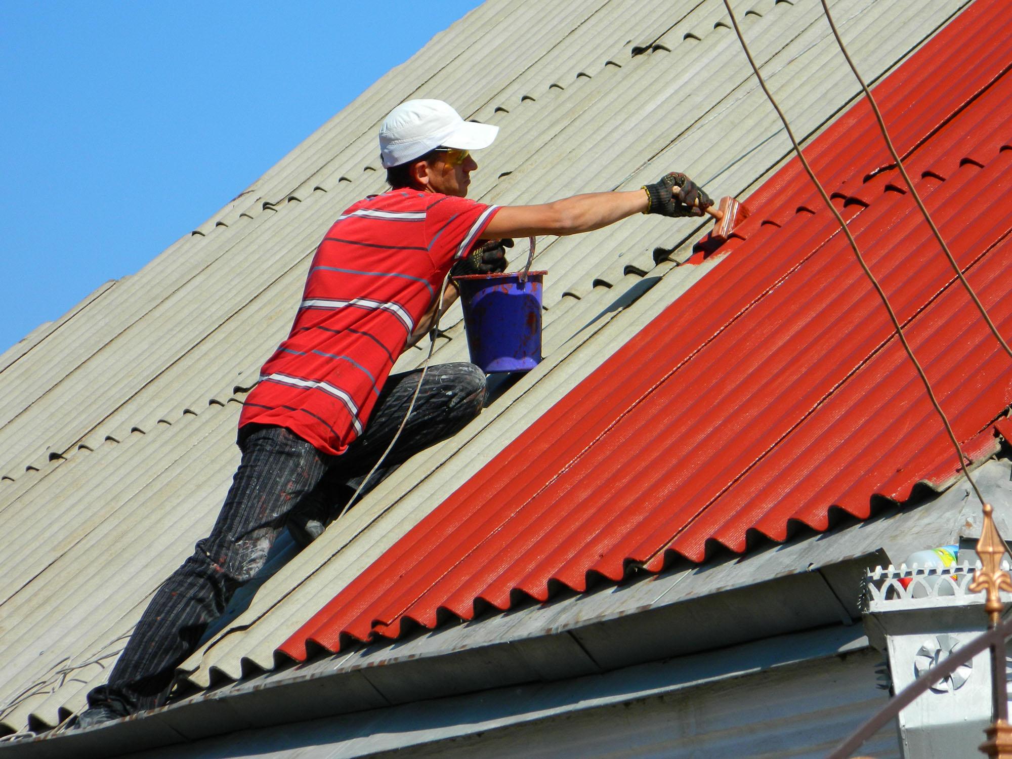 Процесс покраски шиферной крыши дома кистью