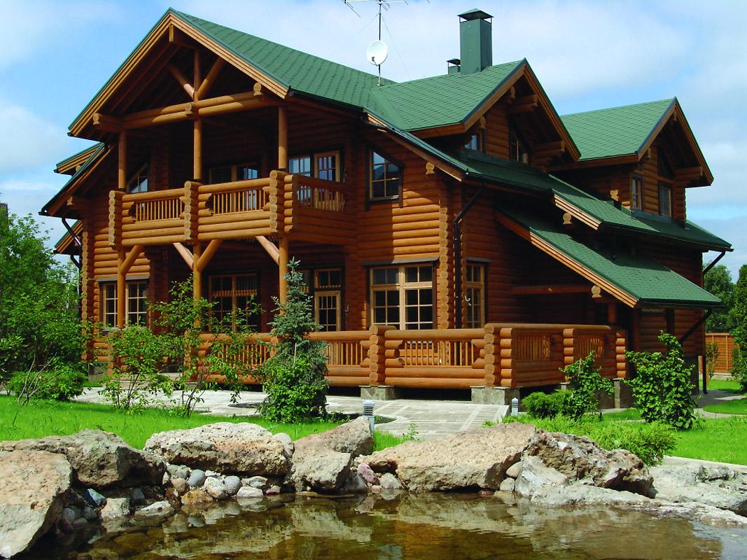 Дом из бруса с зеленой крышей
