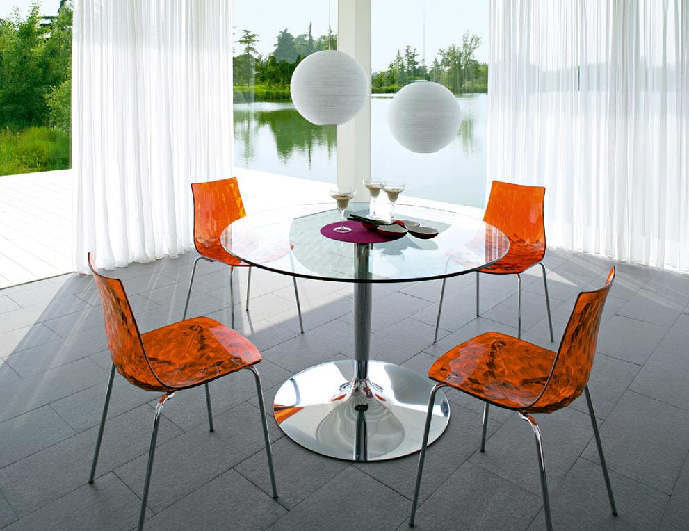 Обеденные стулья из оранжевого стекла и круглый стеклянный стол в интерьере