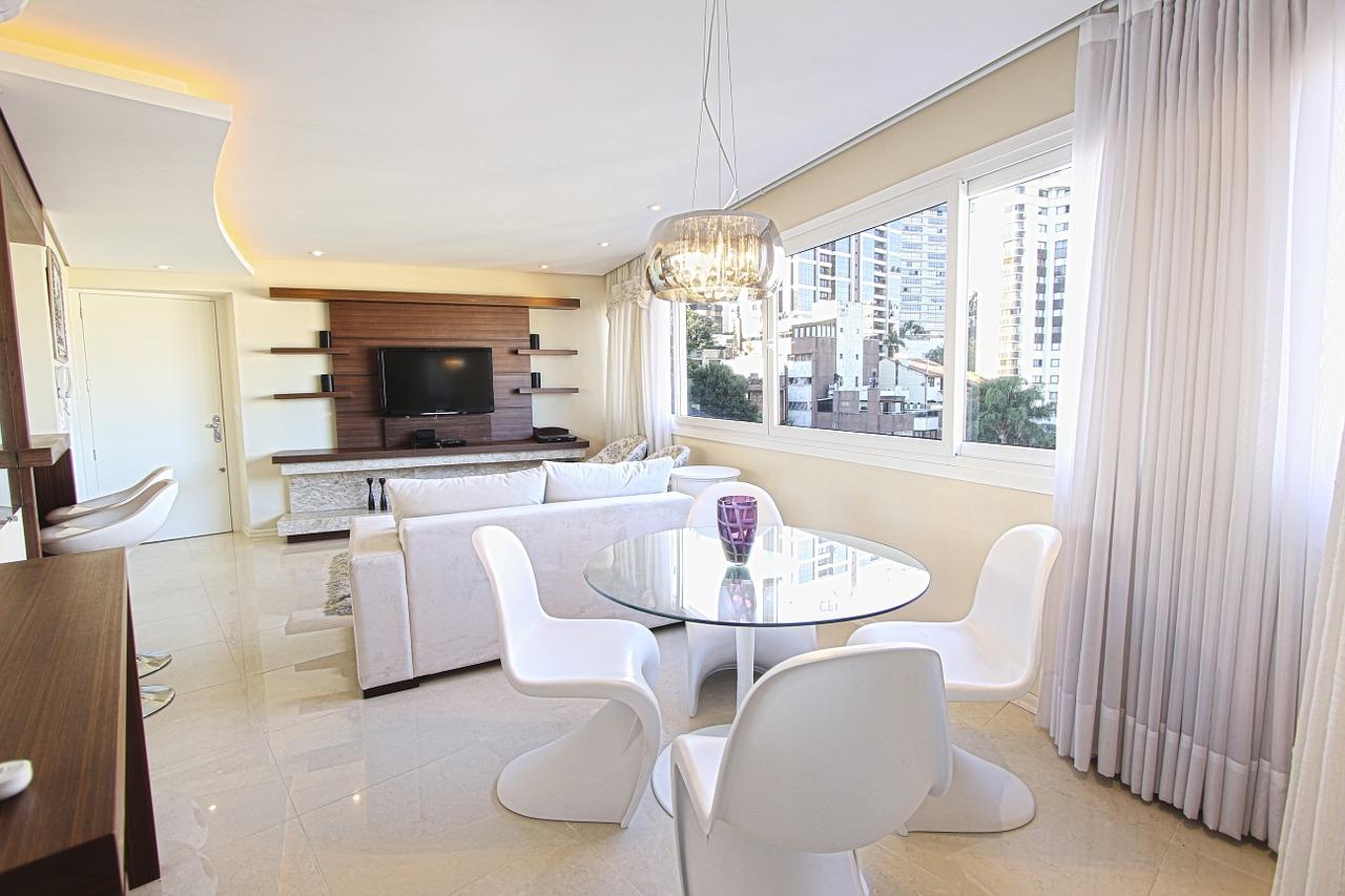 Обеденный стол со стеклянной столешницей в гостиной-кухне