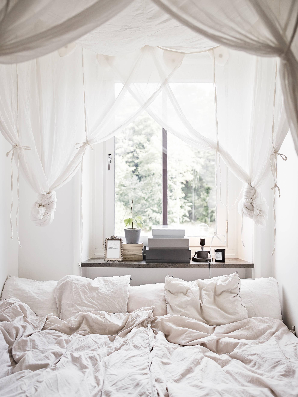 Кровать изголовьем к окну с балдахином
