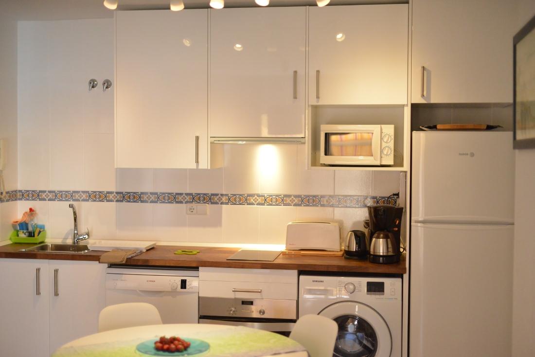 Стиральная машина на белой кухне