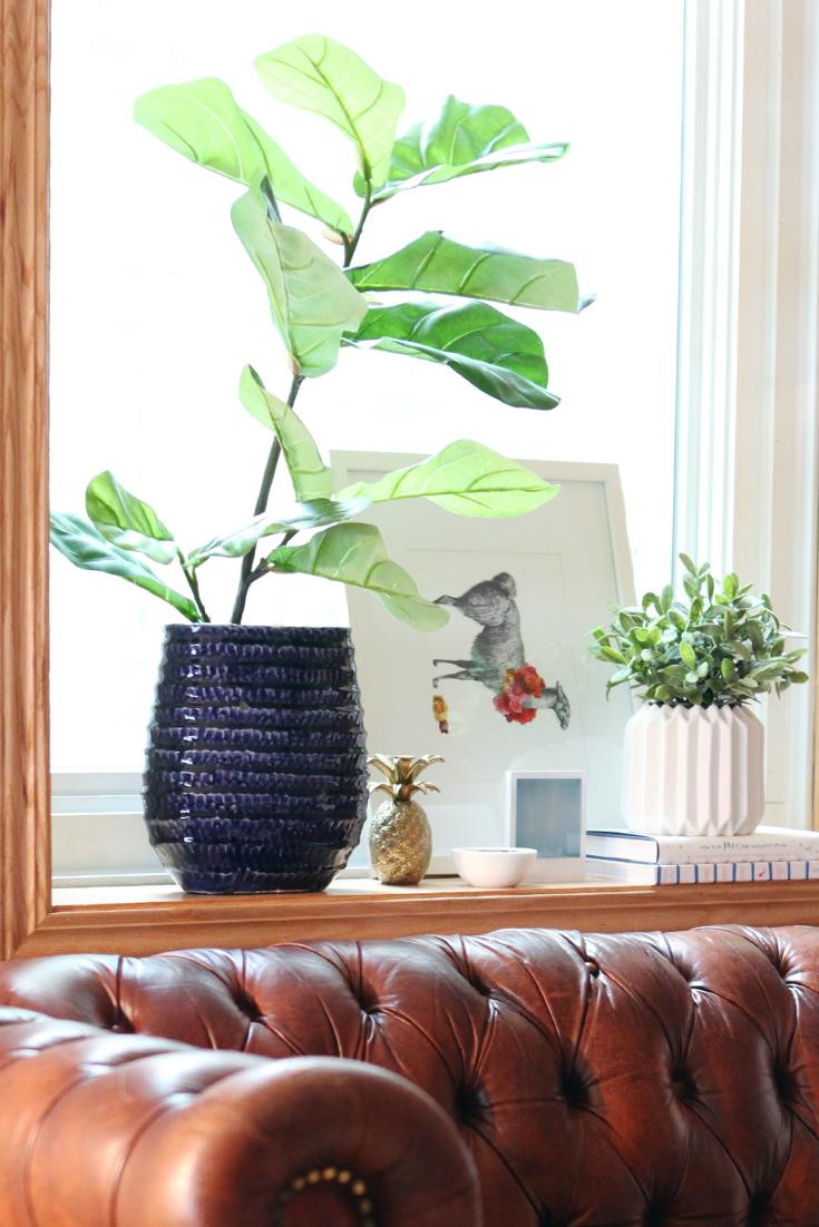 Цветы в декоративных горшках на подоконнике
