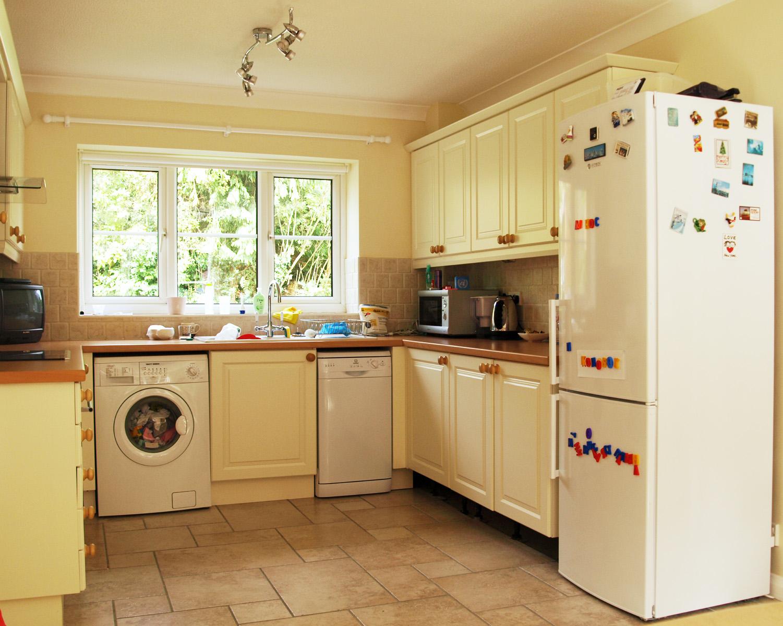 Стиральная машина на кухне с мебелью