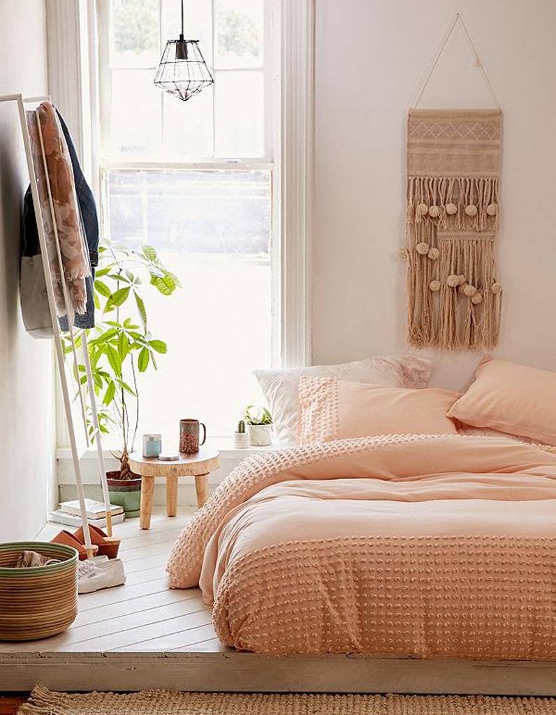 Кровать изголовьем к окну в спальне в пастельных тонах