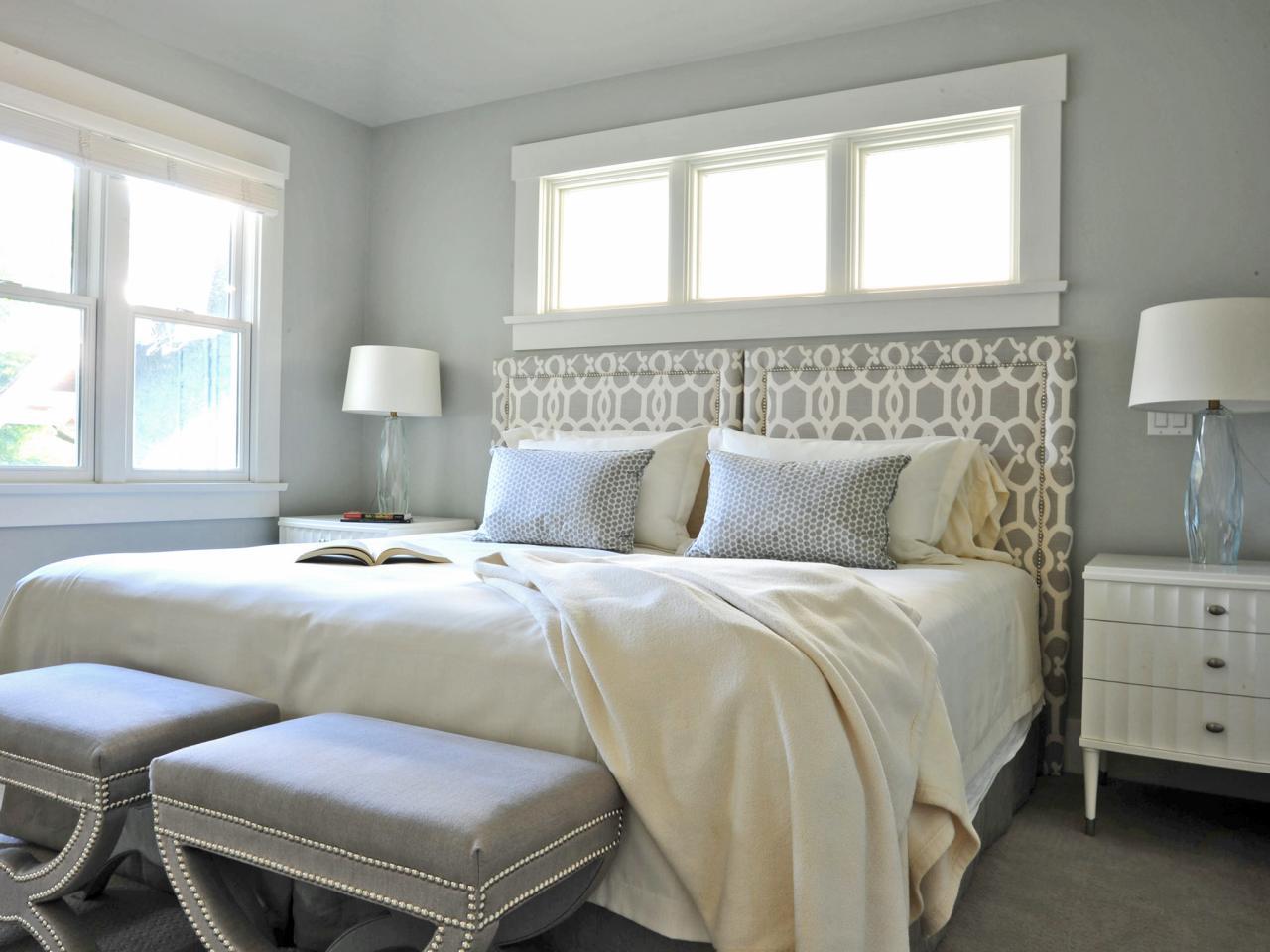 Кровать изголовьем к окну в спальне серой